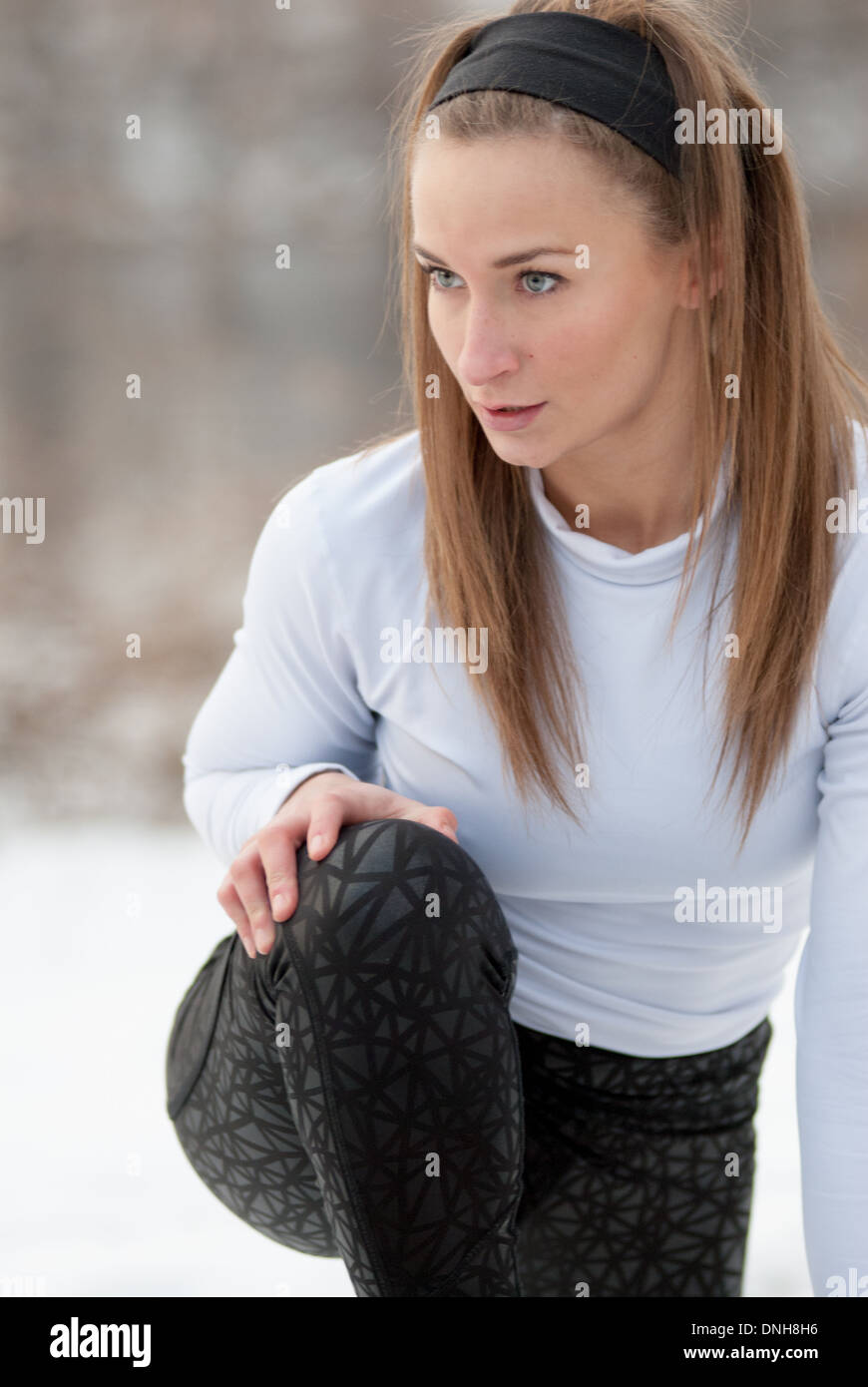 A beautiful young woman stretches before a run on a cold winter day. - Stock Image
