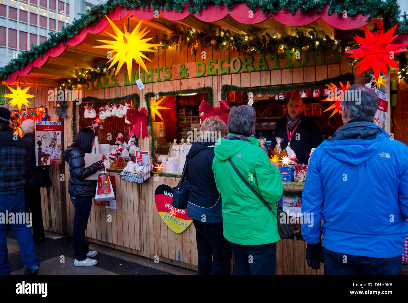 Shoppers visiting a booth selling german christmas lights and stock shoppers visiting a booth selling german christmas lights and decorations at vancouvers outdoor christmas market 2013 aloadofball Image collections