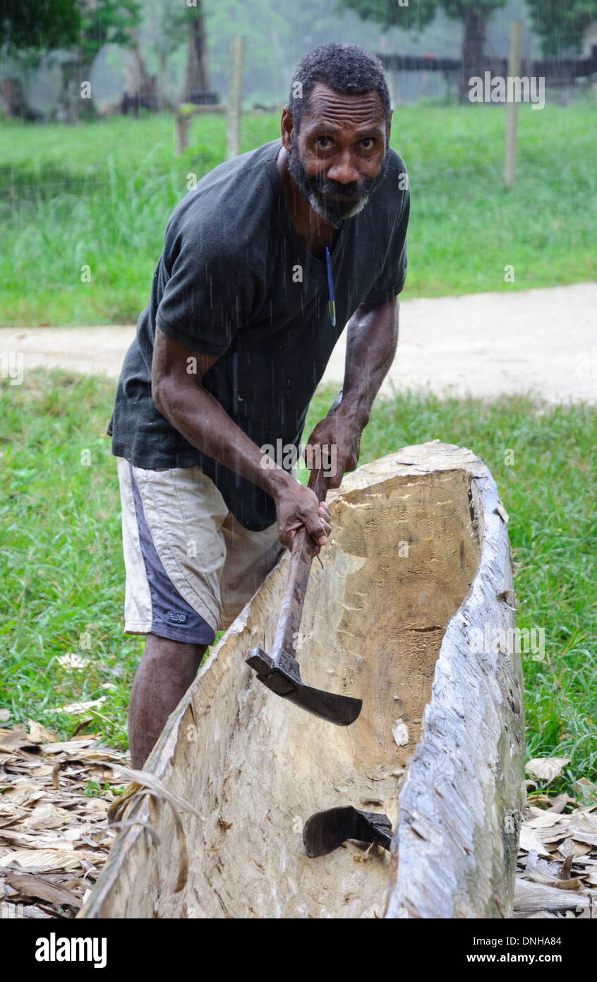 Man making a dugout canoe with an axe, in the traditional way. - Stock Image