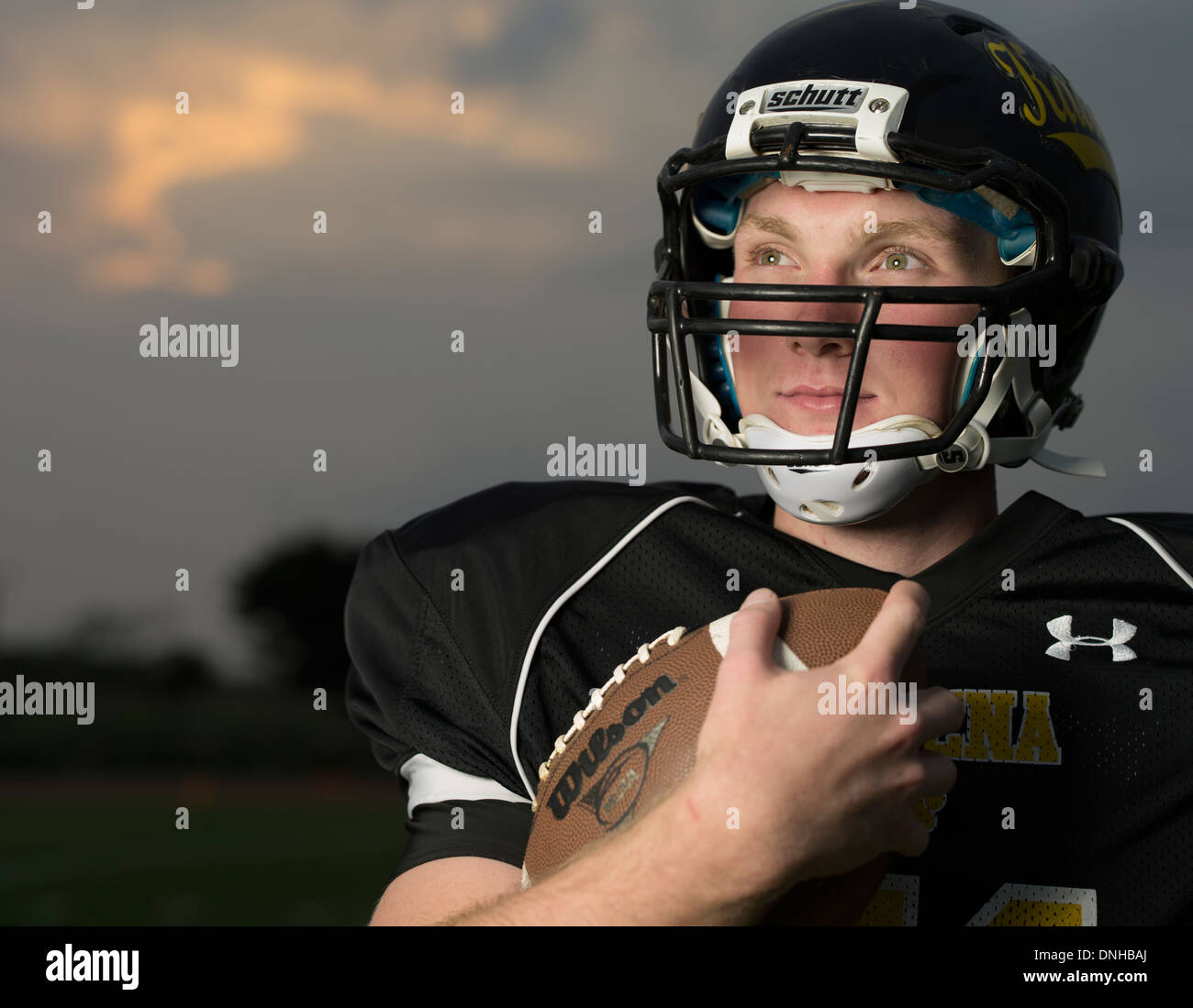 American High School Football Player in uniform with helmet and football. - Stock Image