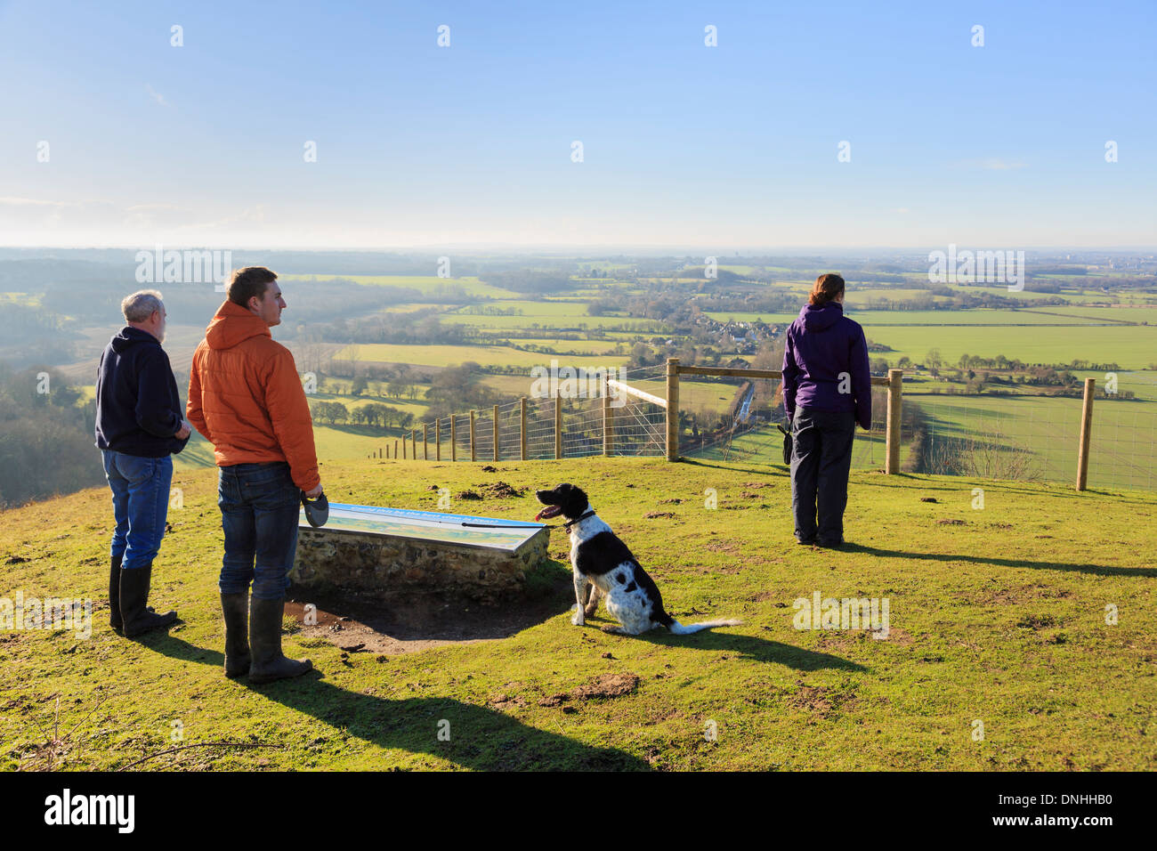 People with dog looking at a view west from viewpoint in Wye National Nature Reserve on North Downs Way in hills near Ashford Kent England UK Britain - Stock Image