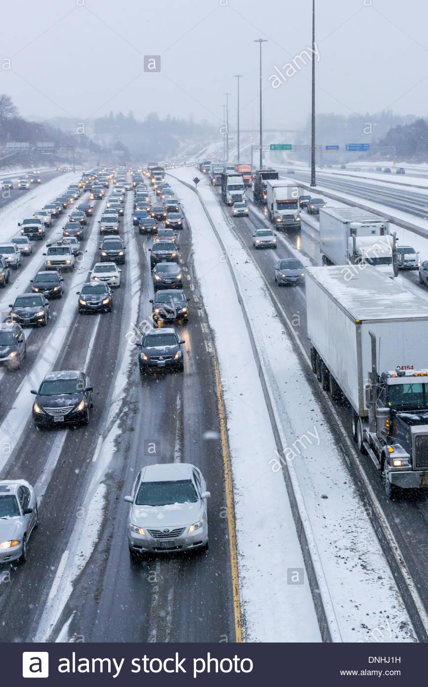 Winter snowstorm backs up towards Toronto morning commutter traffic on Highway 401 in Pickering Ontario Canada - Stock Image