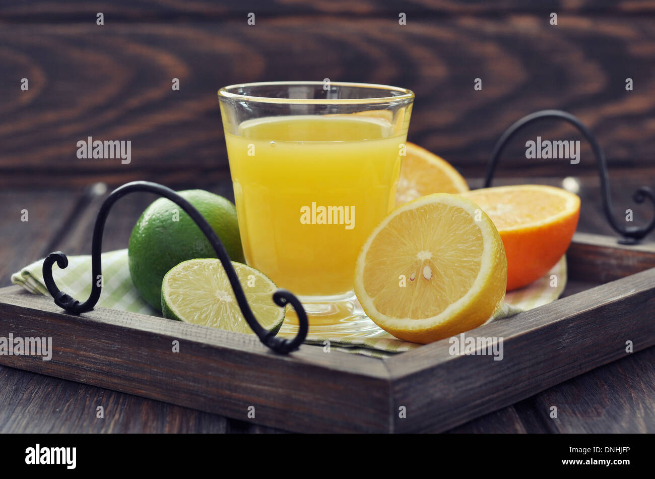 Citrus juice and fruits on vintage tray on wooden background - Stock Image