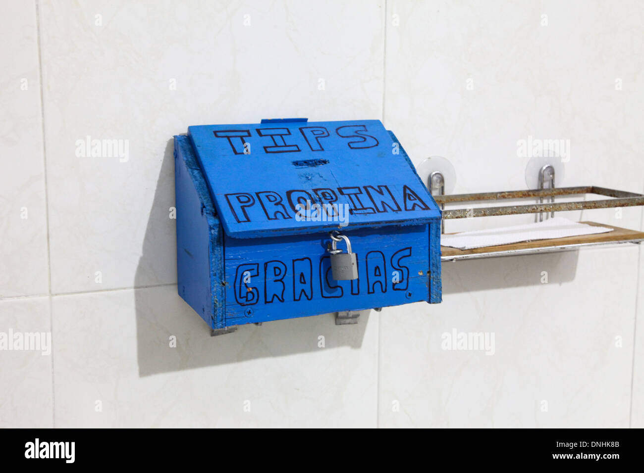 A tip box on a tiled wall with propina and gracias written on it and a pad lock Mexico - Stock Image
