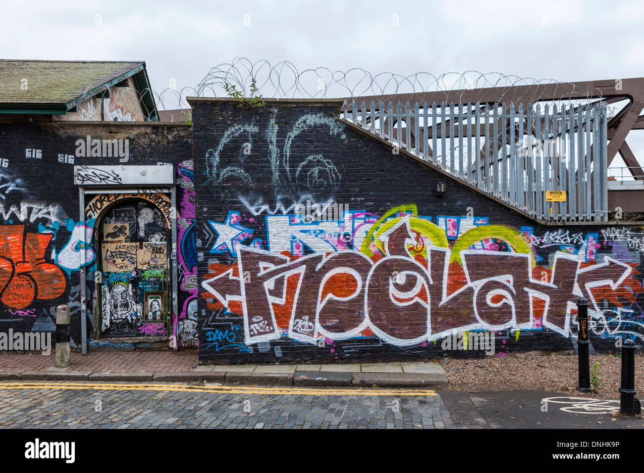 Tags, graffiti, paste ups, barbed wire and fence in Pedley street, off Brick lane, East London, UK - Stock Image