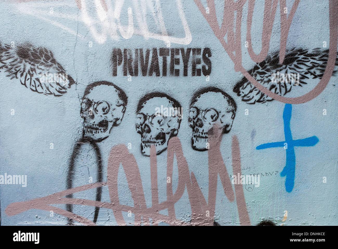 Street stencil art 'Private Eyes' - Three skulls and wings Heneage street - Brick lane, East London, UK - Stock Image