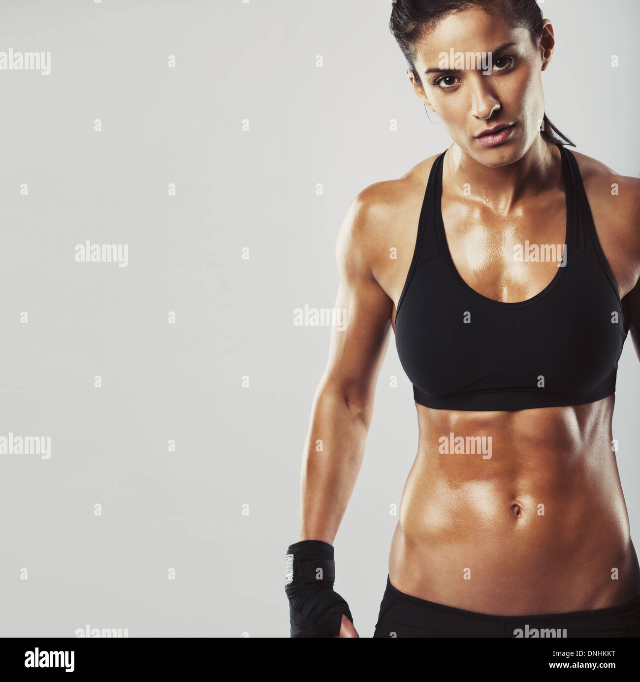 e77fe42179 Picture of a fitness model on grey background. Young woman bodybuilder with  muscular body looking