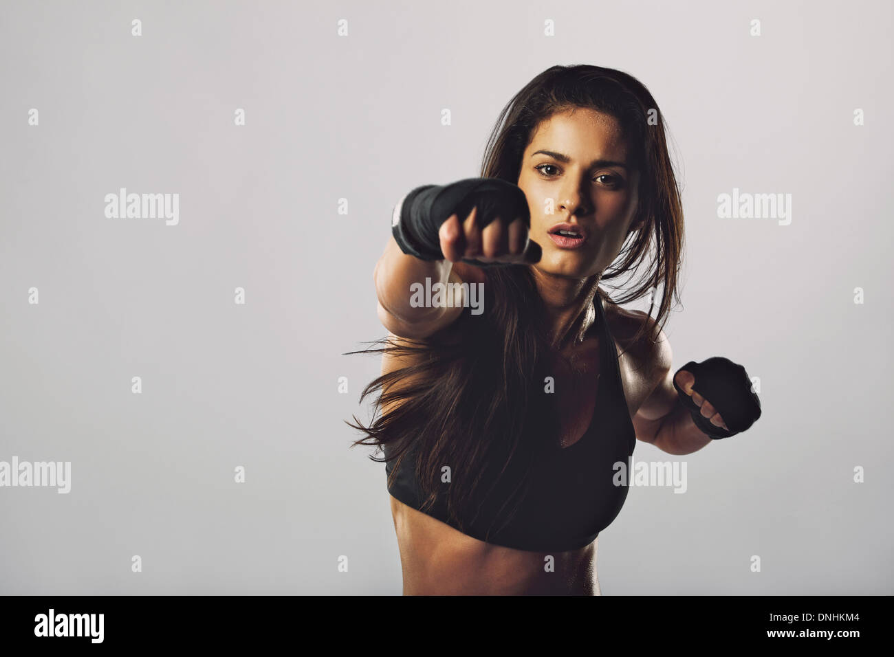 Portrait of hispanic female practicing boxing looking at camera against grey background with copyspace. - Stock Image