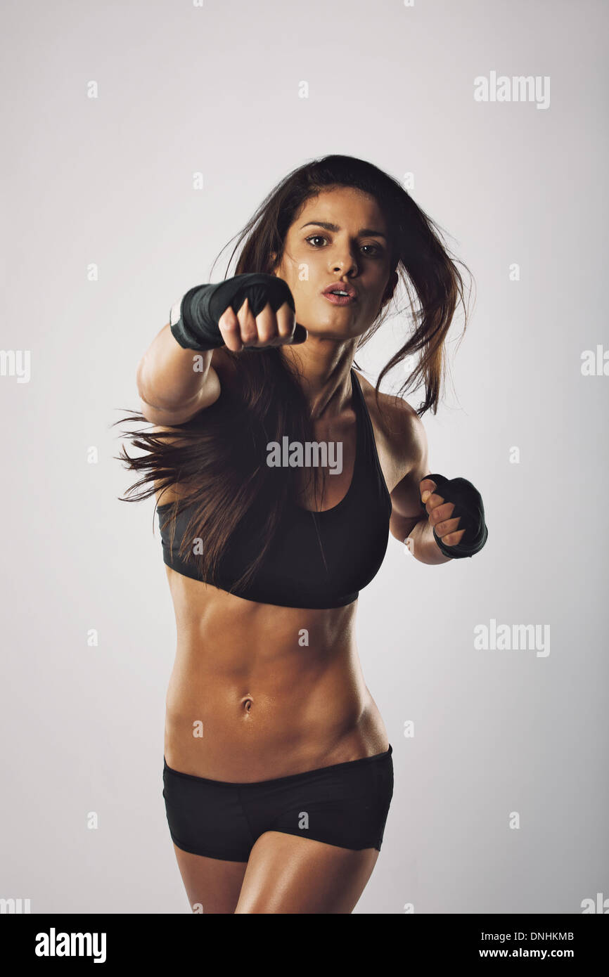 Fit young woman punching towards camera against grey background. Middle eastern female boxer practicing boxing. - Stock Image