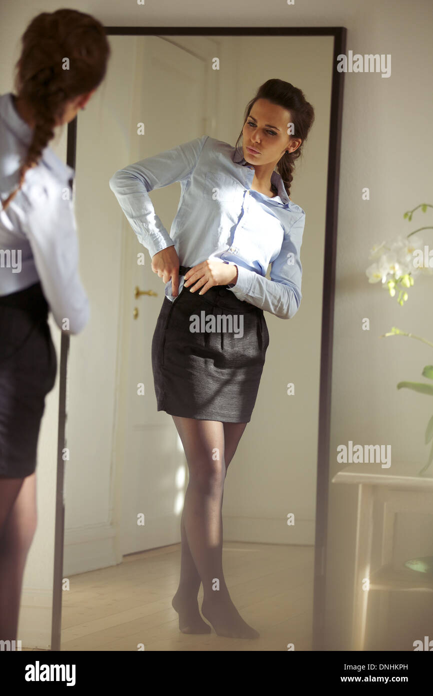 Beautiful young businesswoman fixing her skirt in front of mirror. Pretty caucasian female model getting dressed. - Stock Image