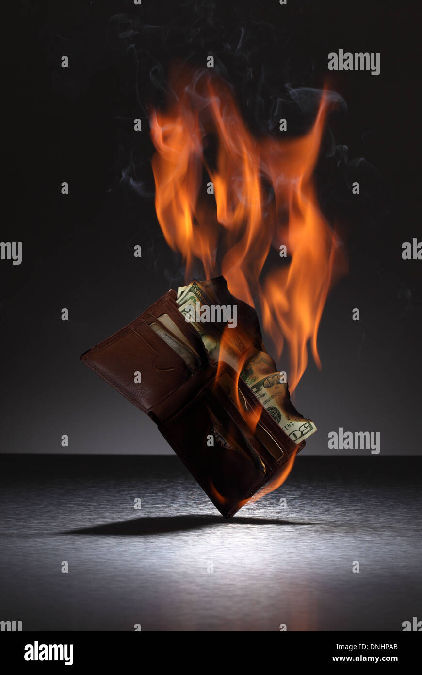 A brown leather wallet filled with credit cards and money on fire. Stock Photo