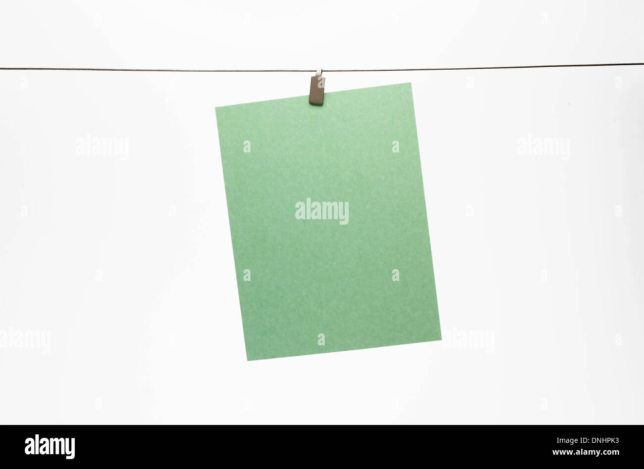 A blank piece of green paper hanging with a clip to a straight wire. White background - Stock Image