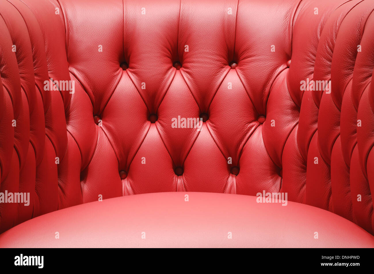 A section of a comfortable red leather sofa chair furniture. - Stock Image