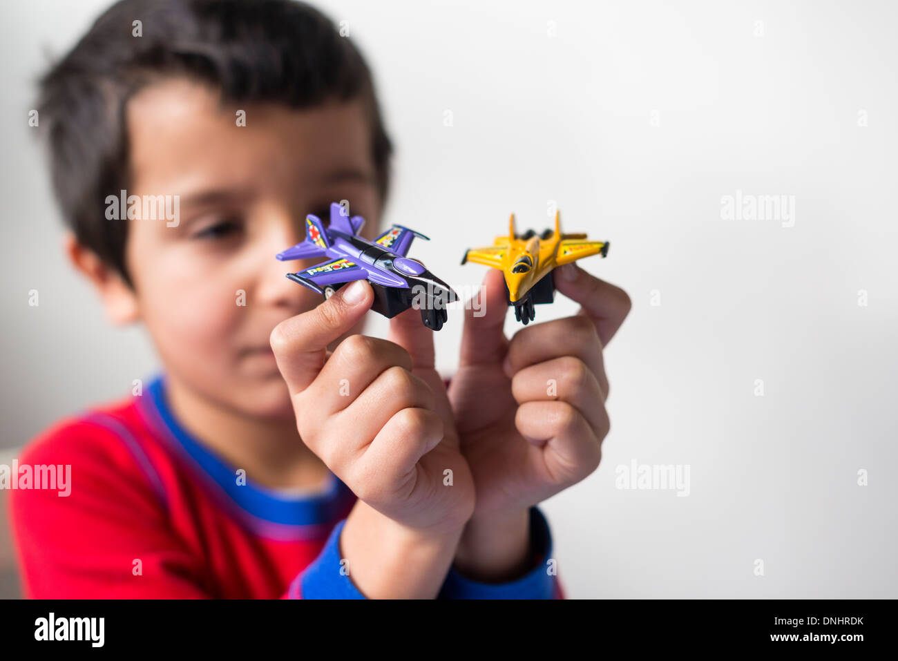Boy plays with two toy aeroplanes - Stock Image
