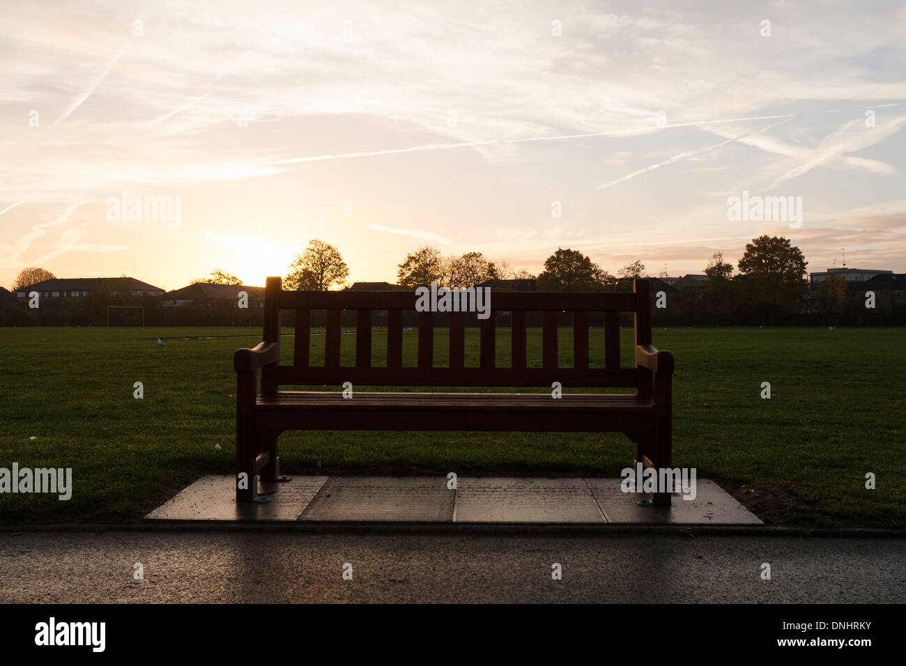 A bench alongside a path in the Gibbons Recreation Grounds in Willesden, London. - Stock Image