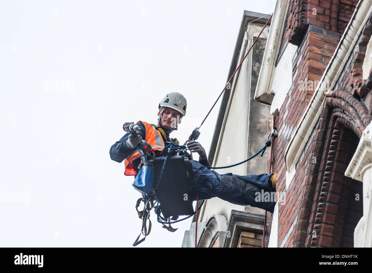Specialist jobs: Workman carrying tools abseiling down the exterior of a building in London in a safety harness Stock Photo