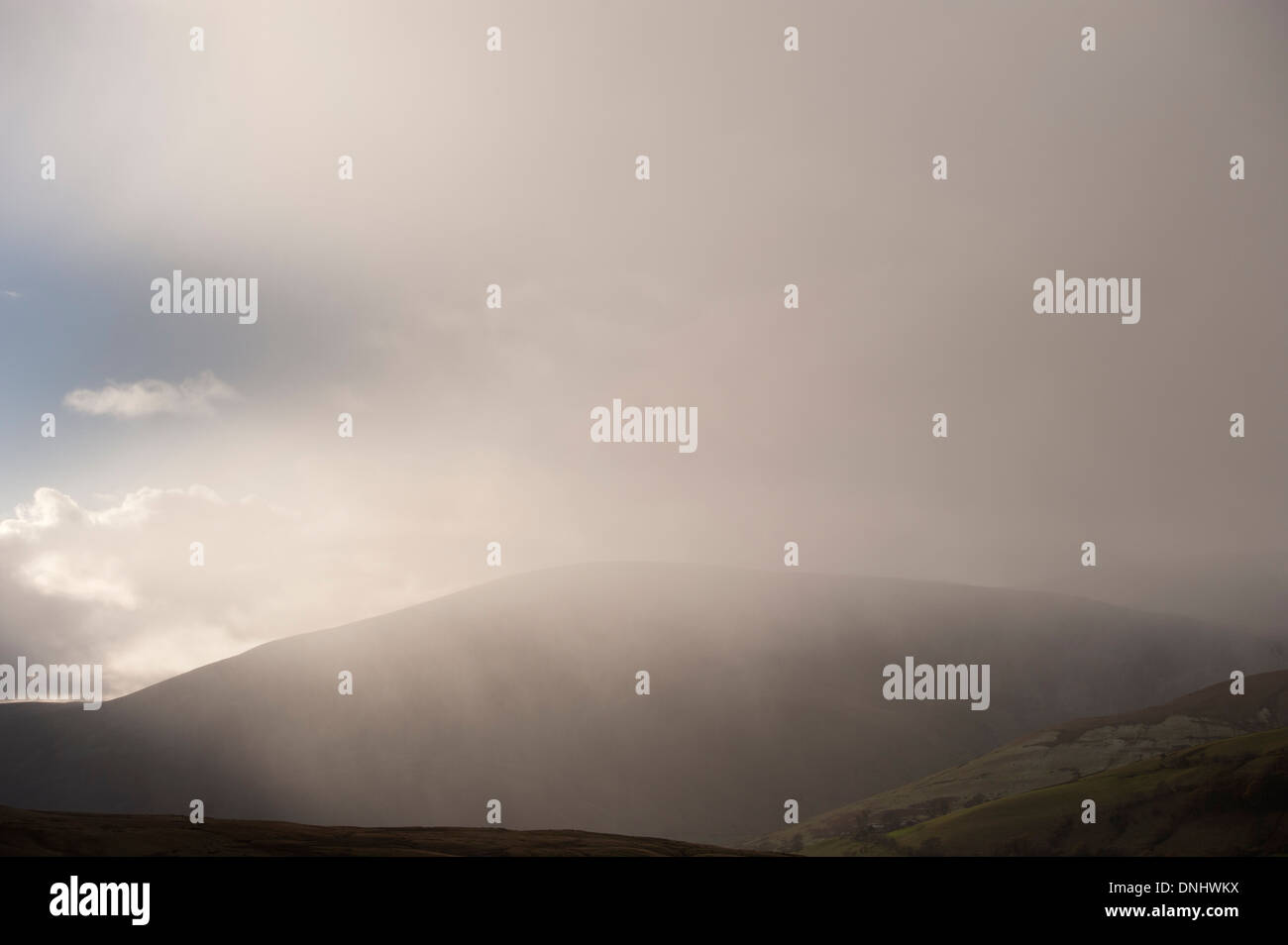 Wintery shower falling in hills, Cumbria, UK. - Stock Image