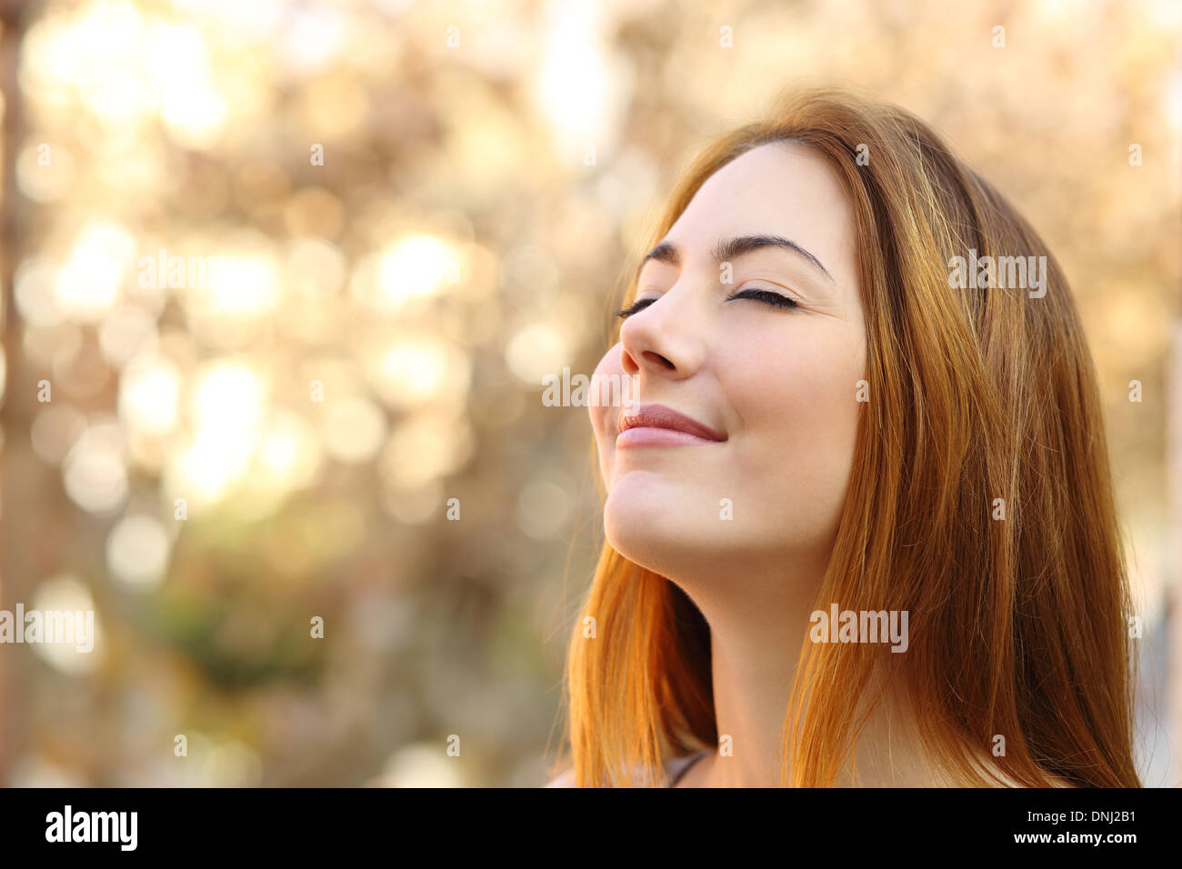 Portrait of a beautiful woman doing breath exercises with an autumn unfocused background - Stock Image