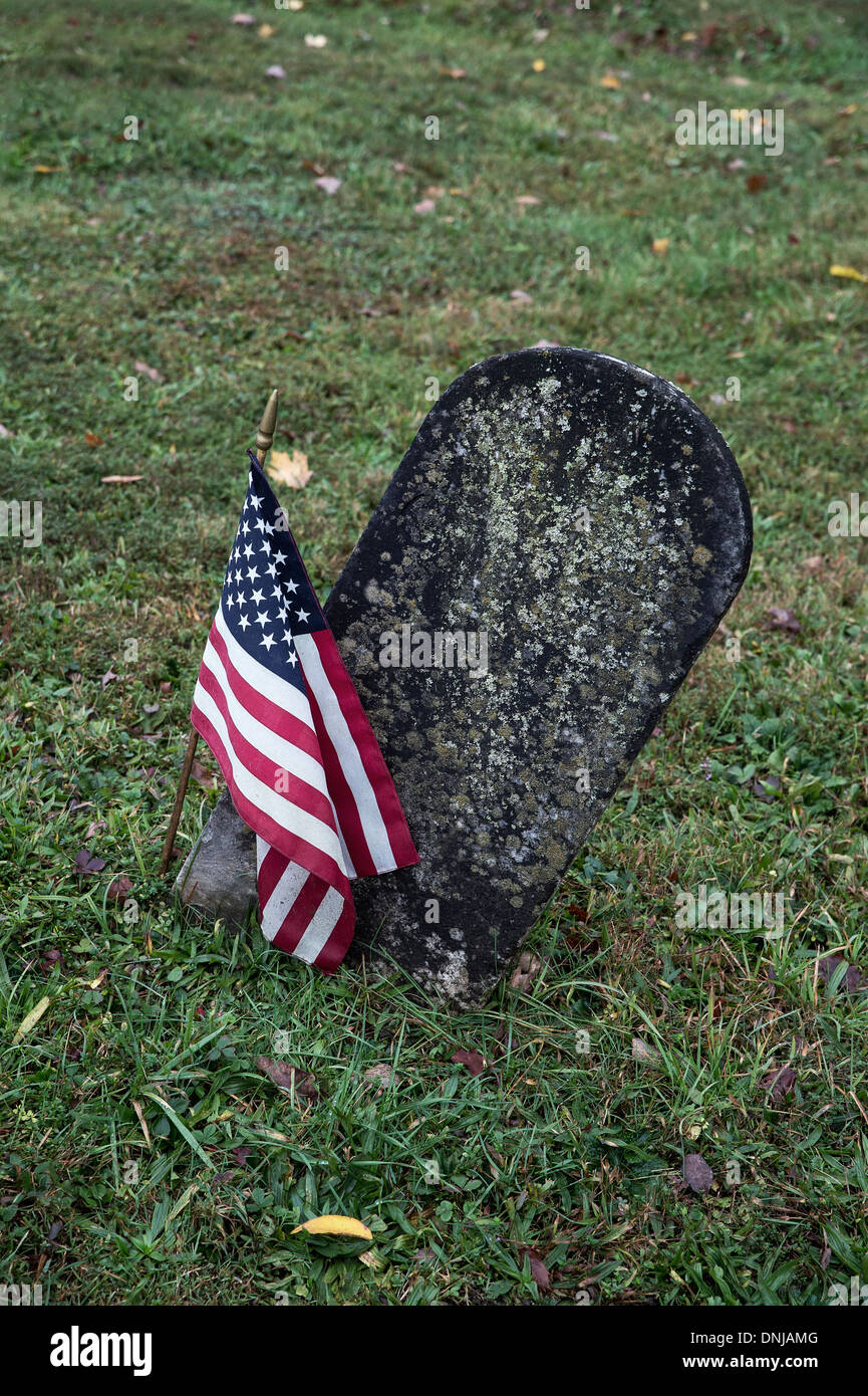 Grave stone with American flag. - Stock Image