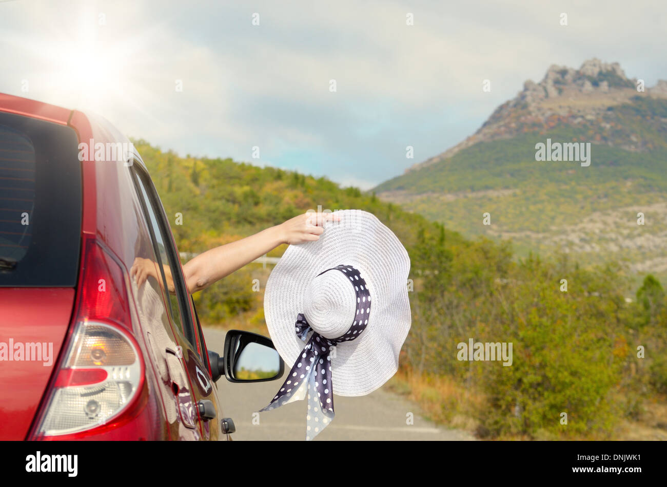 Woman shows sun hat from car window with mountains at background. Travel vacations concept. - Stock Image