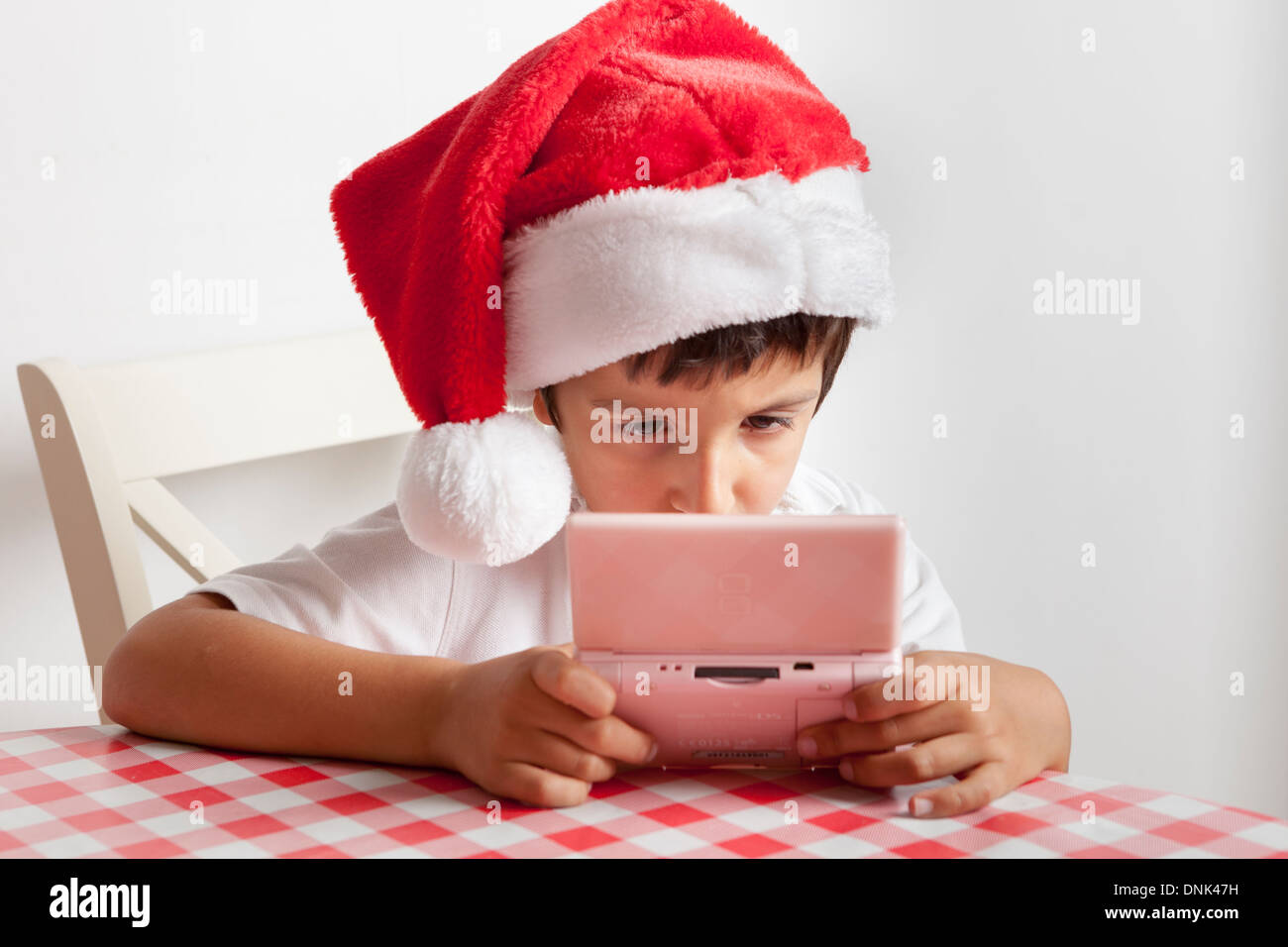 Boy in Santa's hat plays on Nintendo DS - Stock Image