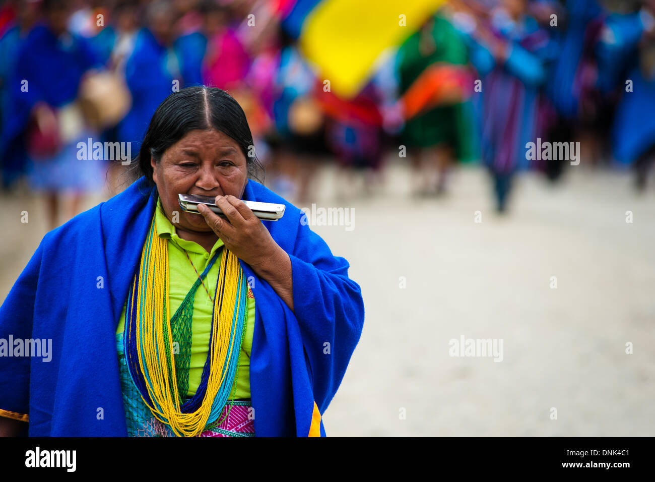 A native woman from the Kamentsá tribe plays harmonica during the Carnival of Forgiveness in Sibundoy, Colombia. - Stock Image