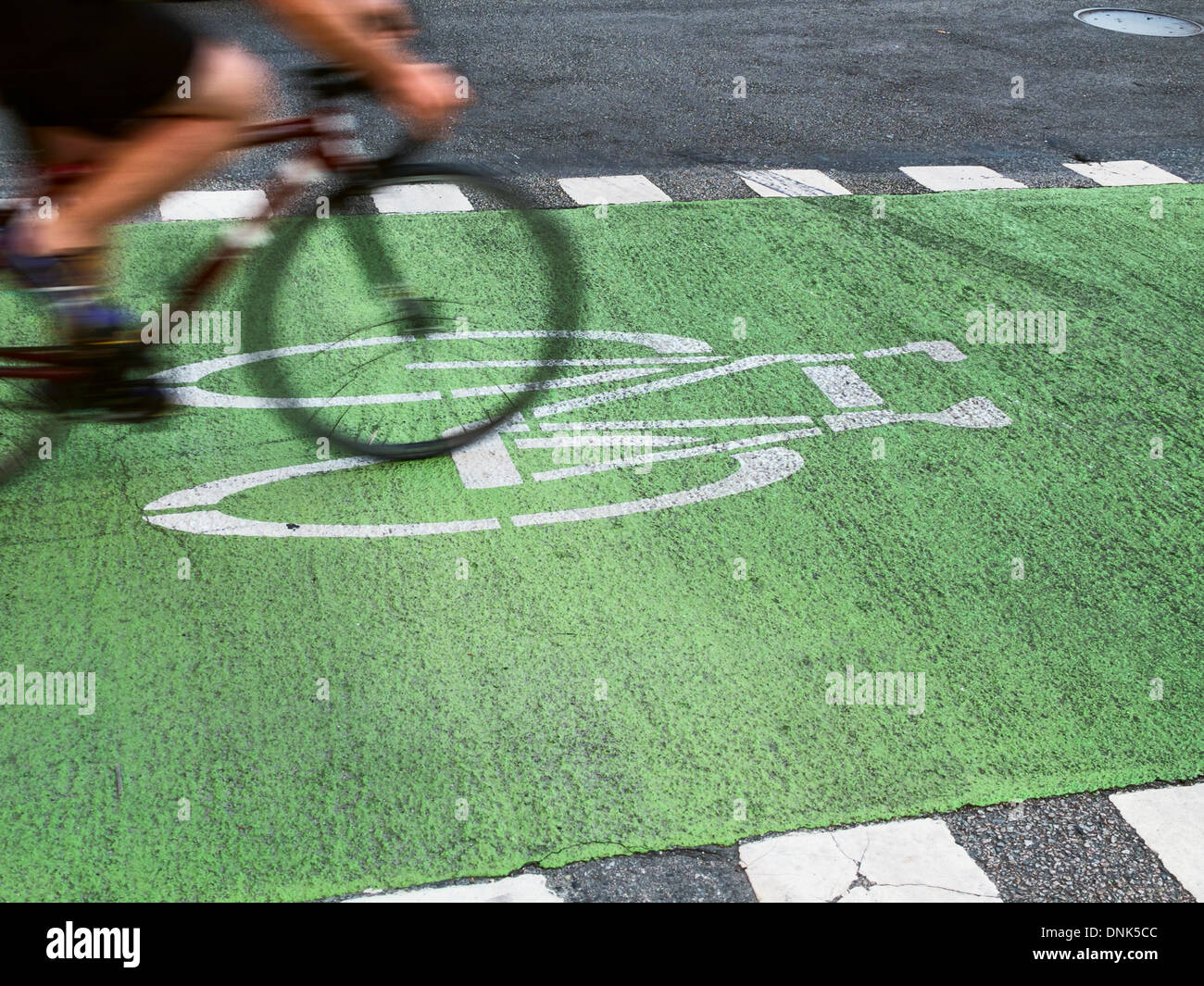 A lone cyclist rides their bike in a dedicated bike lane. - Stock Image