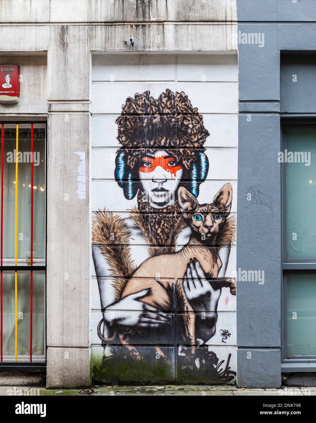 Street urban art Tribal Woman in mask holding sphynx hairless cat - Cheshire street, East London, UK - Stock Image