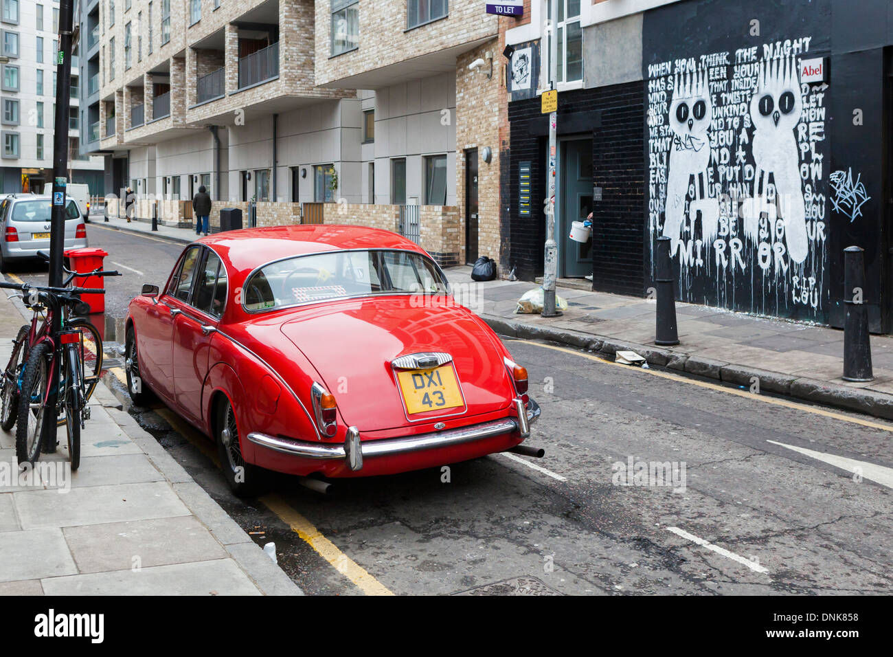 Red classic parked car and owls, street art by Dscreet - Bacon street, off Brick lane, East London, UK - Stock Image
