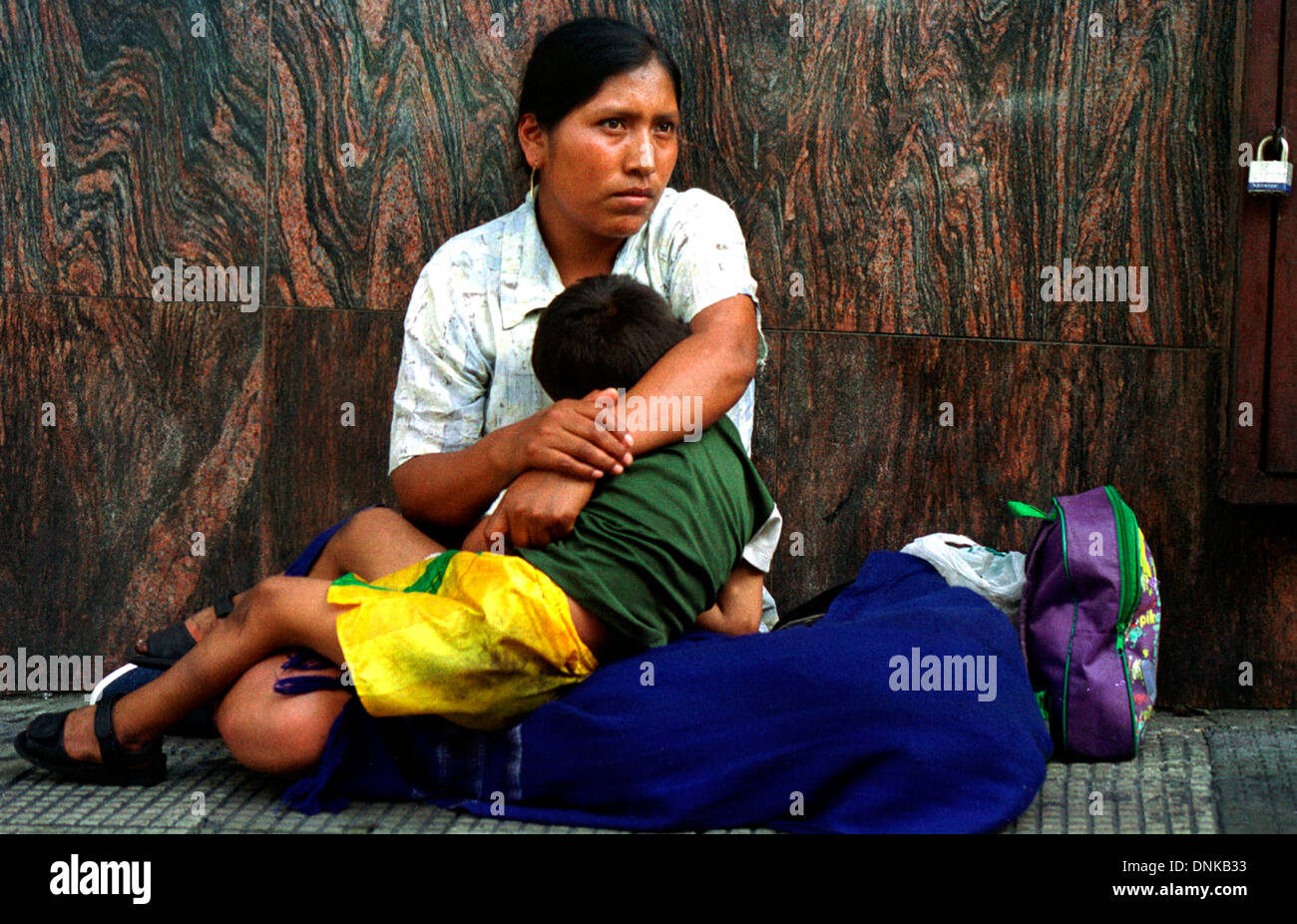 An indigenous Colombian refugee and her son, from Colombia's Cauca Departament, beg for money in Caracas - Stock Image