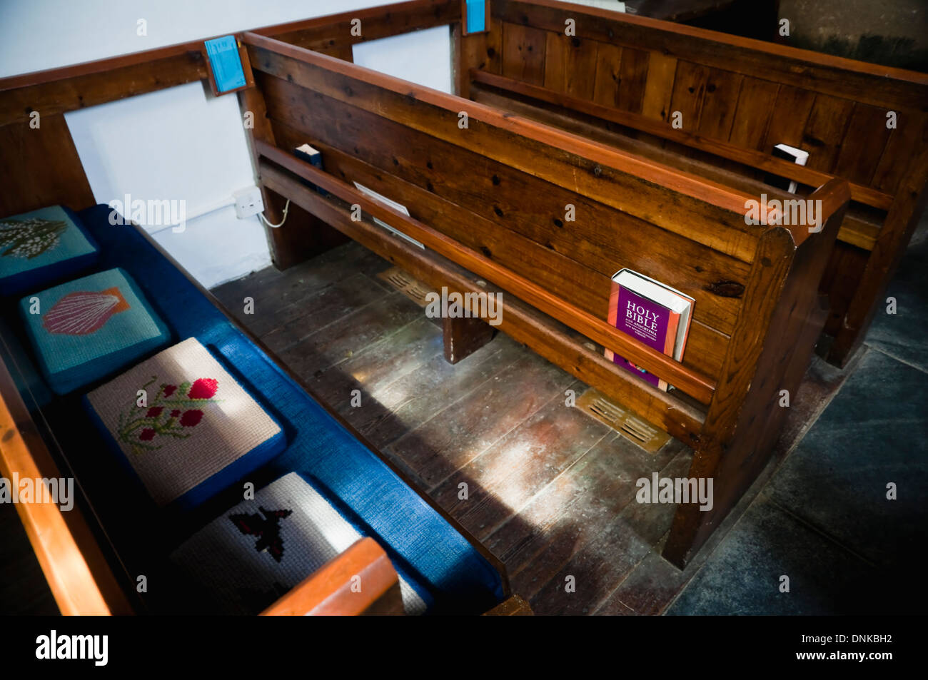 Church Pews with kneelers and Bible in an English Country Church. UK. Stock Photo