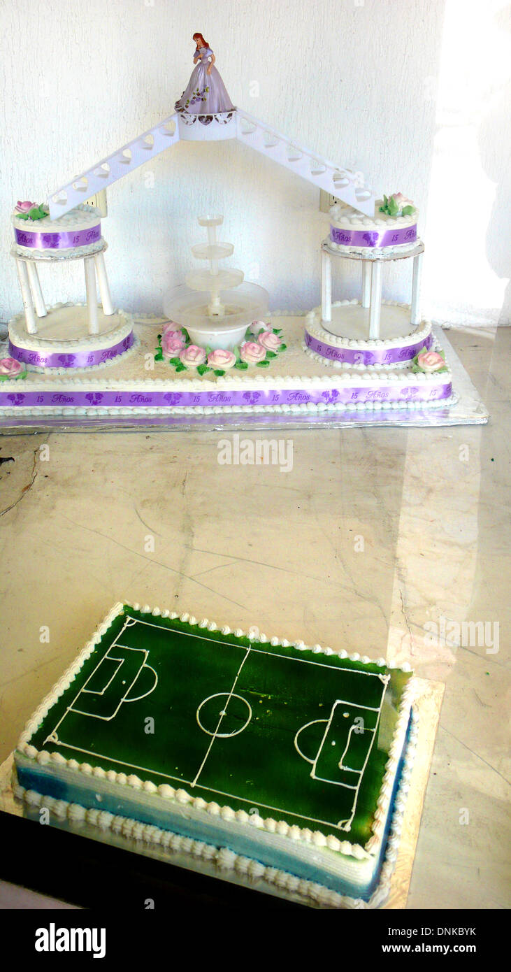 A cake decorated as a soccer field, below, and another decorated for a coming-of-age party for a fifteen year old girl called 'Q - Stock Image