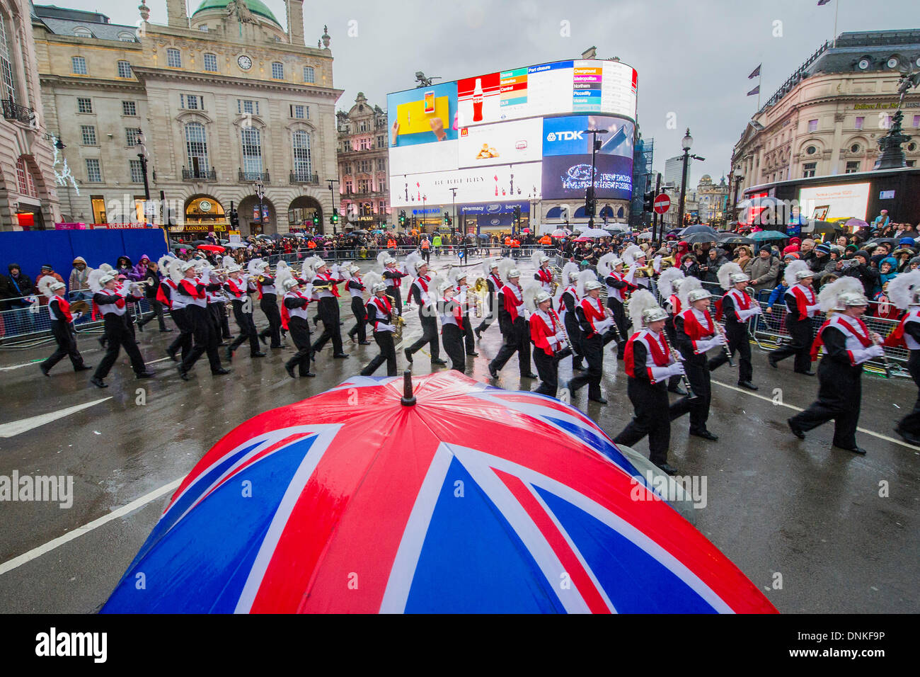 London, UK. 01st Jan, 2014. A new year's day parade passes through Piccadilly Circus on a wet and windy day. London, Stock Photo