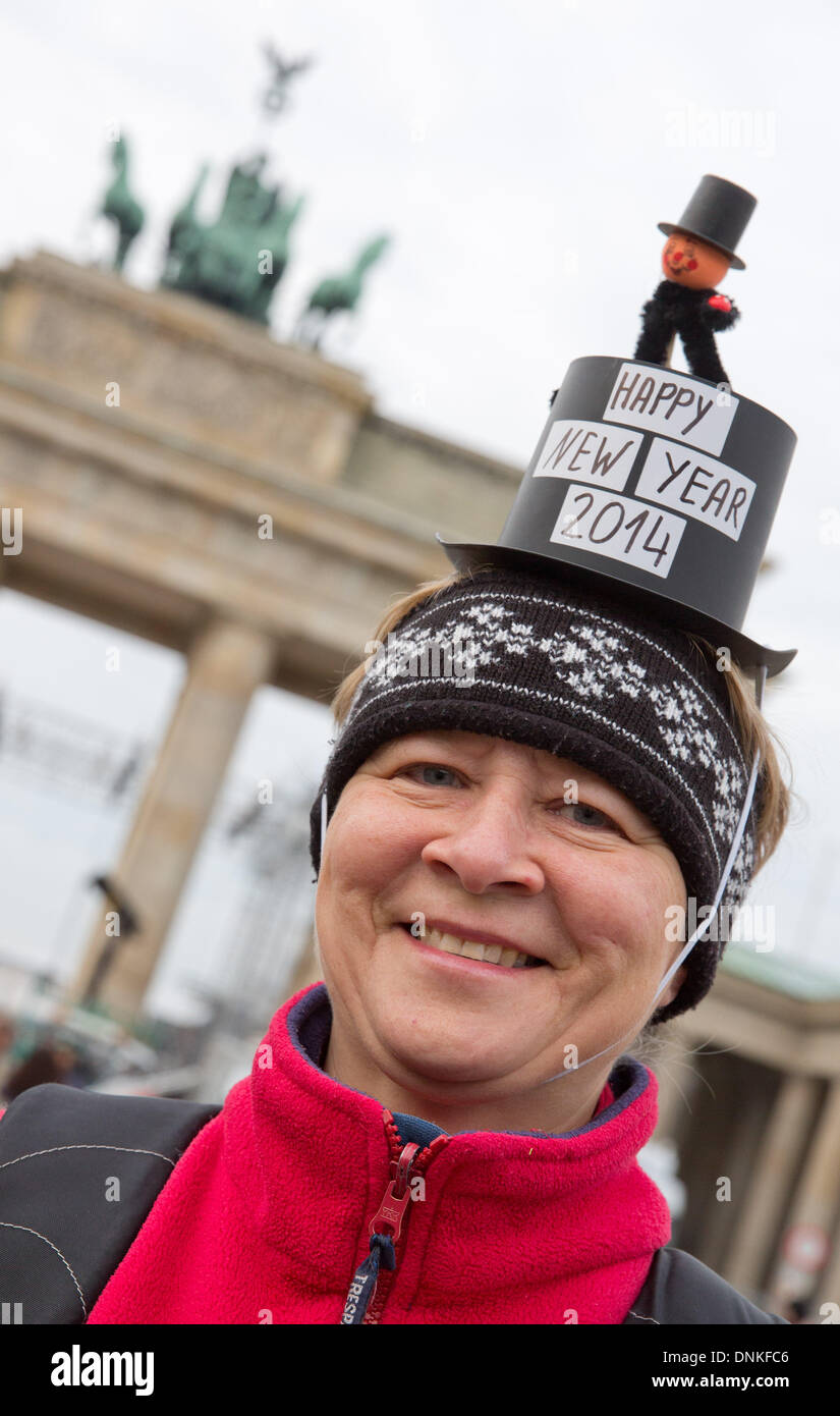 Berlin, Germany. 01st Jan, 2014. Susanne Gerth, a volunteer of the New Year's Run, poses in front of the Brandenburg Gate wearing a New Year's hat in Berlin, Germany, 01 January 2014. People from all over the world gathered along the historical Straße des 17. Juni (17th of June Street) to ring in the year 2014. Photo: JOERG CARSTENSEN/dpa/Alamy Live News - Stock Image