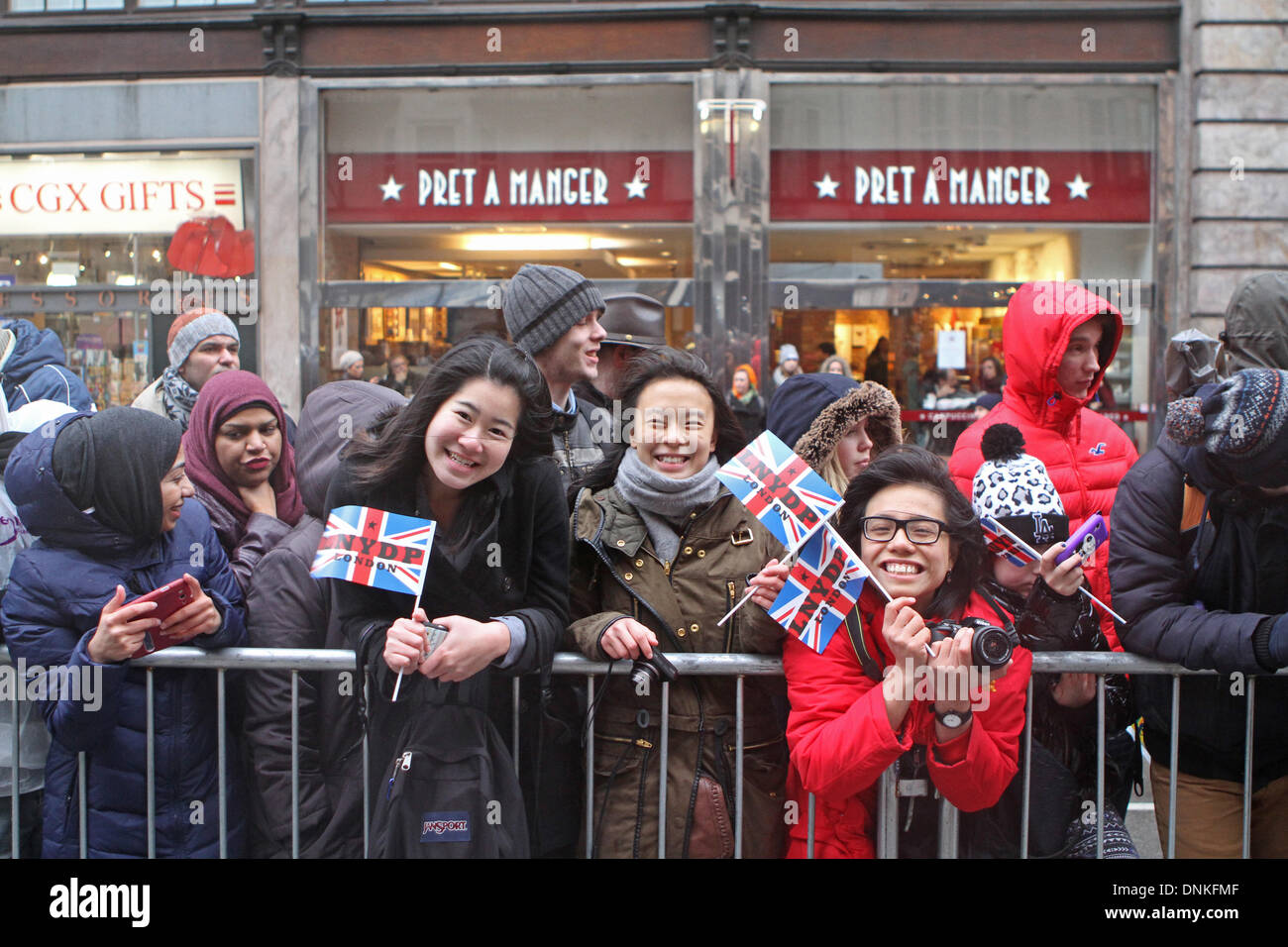 London,UK,1st January 2014,Crowds smile despite the rain waiting for the London's New Year's Day Parade 2014 Credit: Keith Larby/Alamy Live News - Stock Image