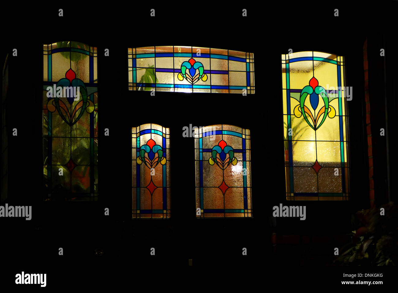 Stained glass windows on the porch of an Edwardian house illuminated from behind by house lights. - Stock Image