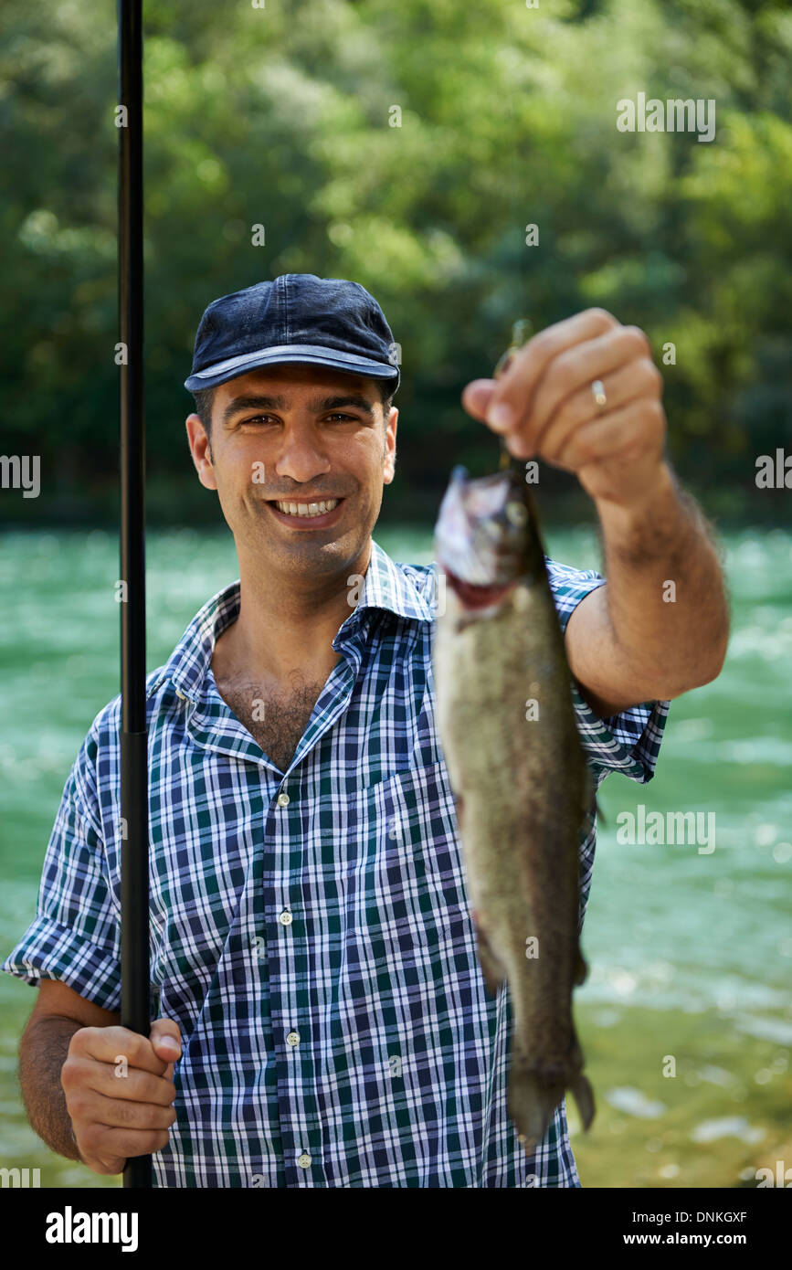 mid adult fisherman on holidays on river, relaxing and fishing trout. Focus on background - Stock Image