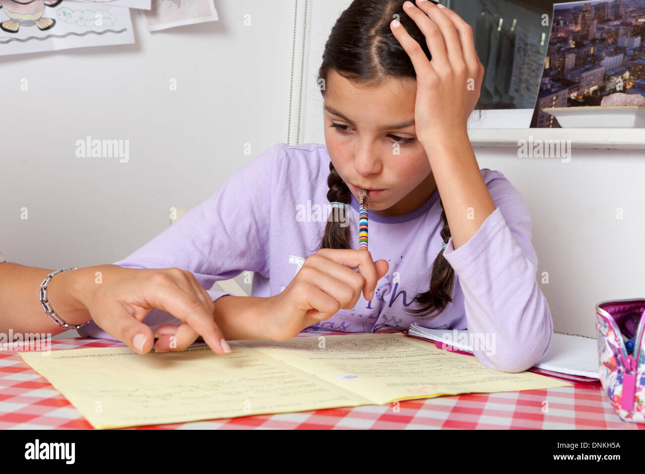 Parent helping schoolgirl with homework - Stock Image