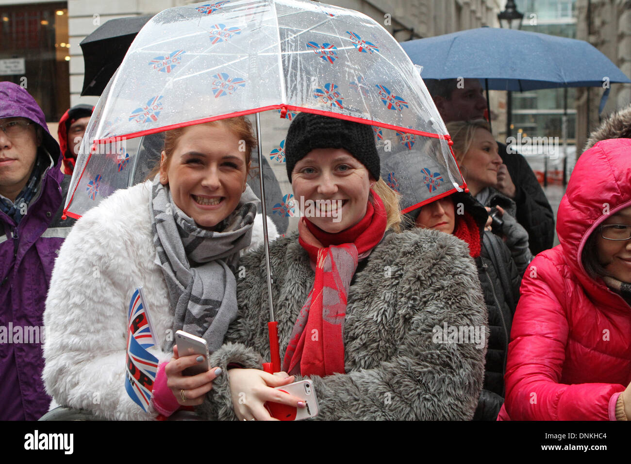 London,UK,1st January 2014,Sheltering under an umbrella at the London's New Year's Day Parade 2014 Credit: Keith Larby/Alamy Live News - Stock Image