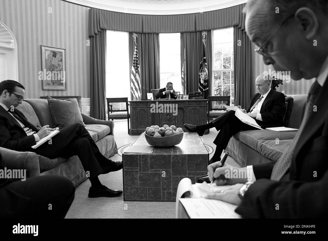US President Barack Obama sips a cup of tea while talking on the phone with Chinese President Xi Jinping in the Oval Office of the White House March 14, 2013 in Washington, DC. - Stock Image