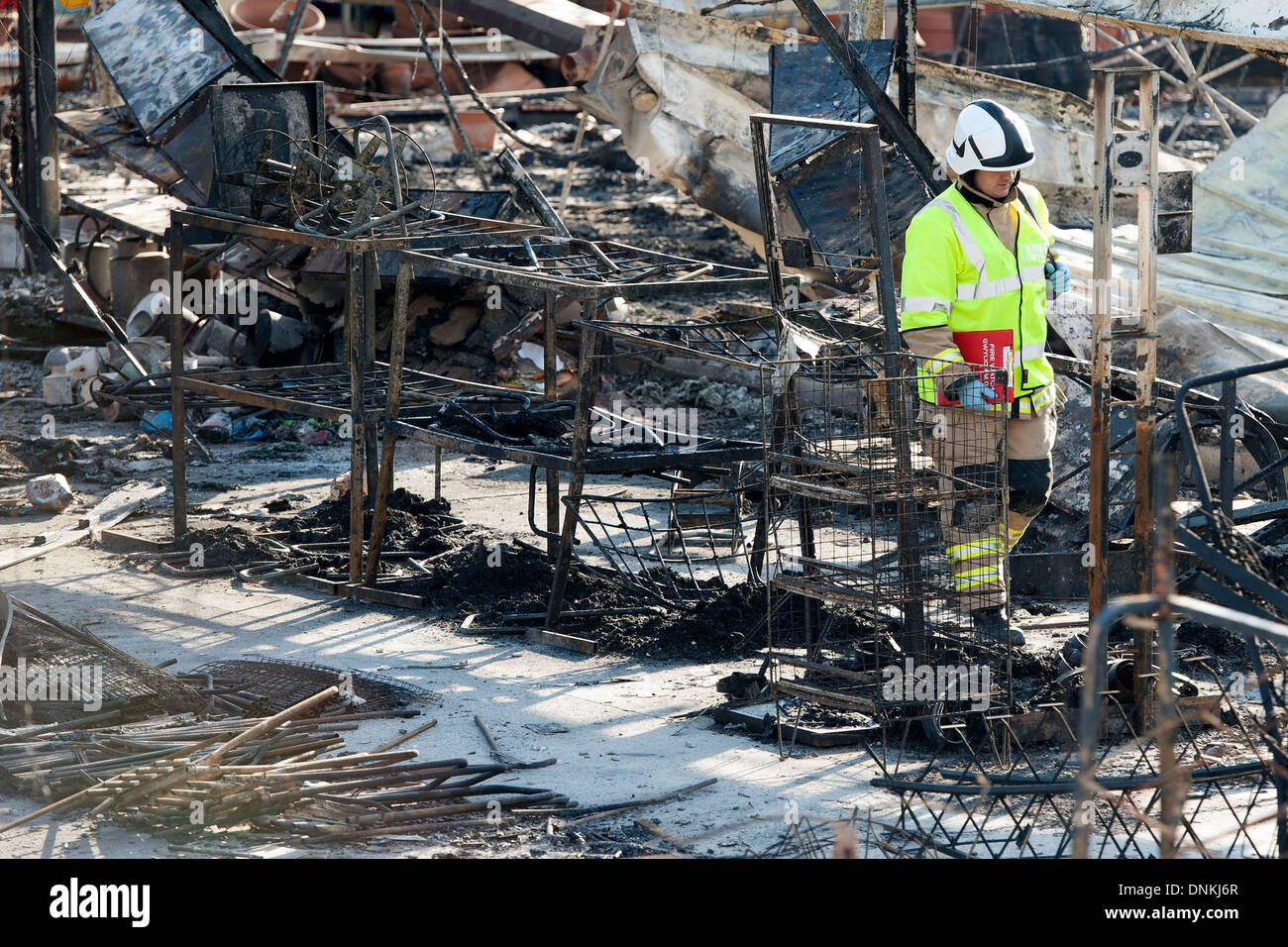 A fire investigator walks through the scene of a fire. - Stock Image