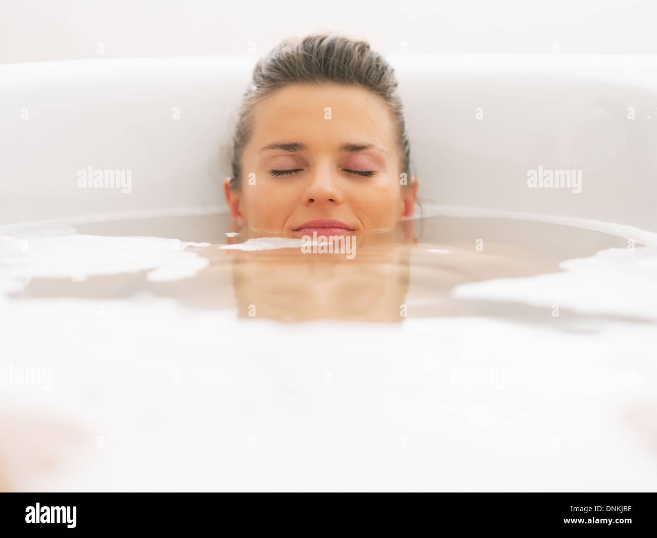Young woman laying under water in bathtub - Stock Image