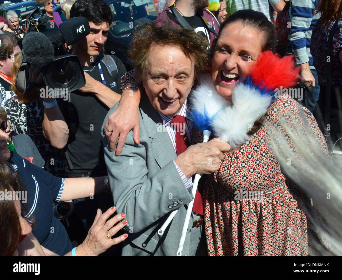 Ken Dodd posing with a fan in Knotty Ash, Liverpool during the 2012 Olympic Torch relay. - Stock Image