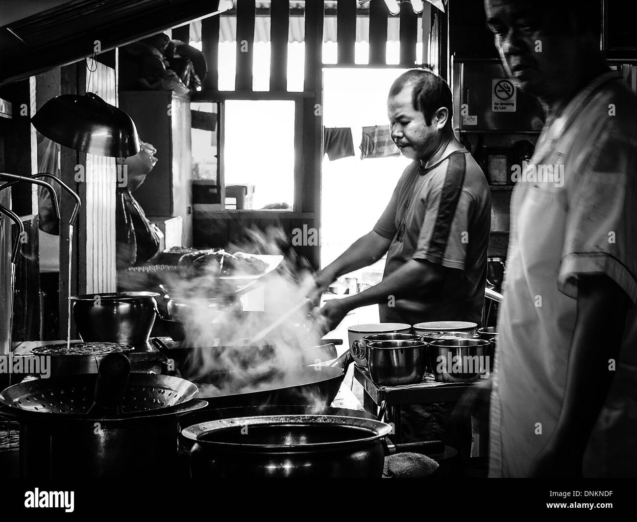 The master chef watches his apprentice cook the noodle dish Char Kway Teow on Pulau Ubin Island in Singapore - Stock Image