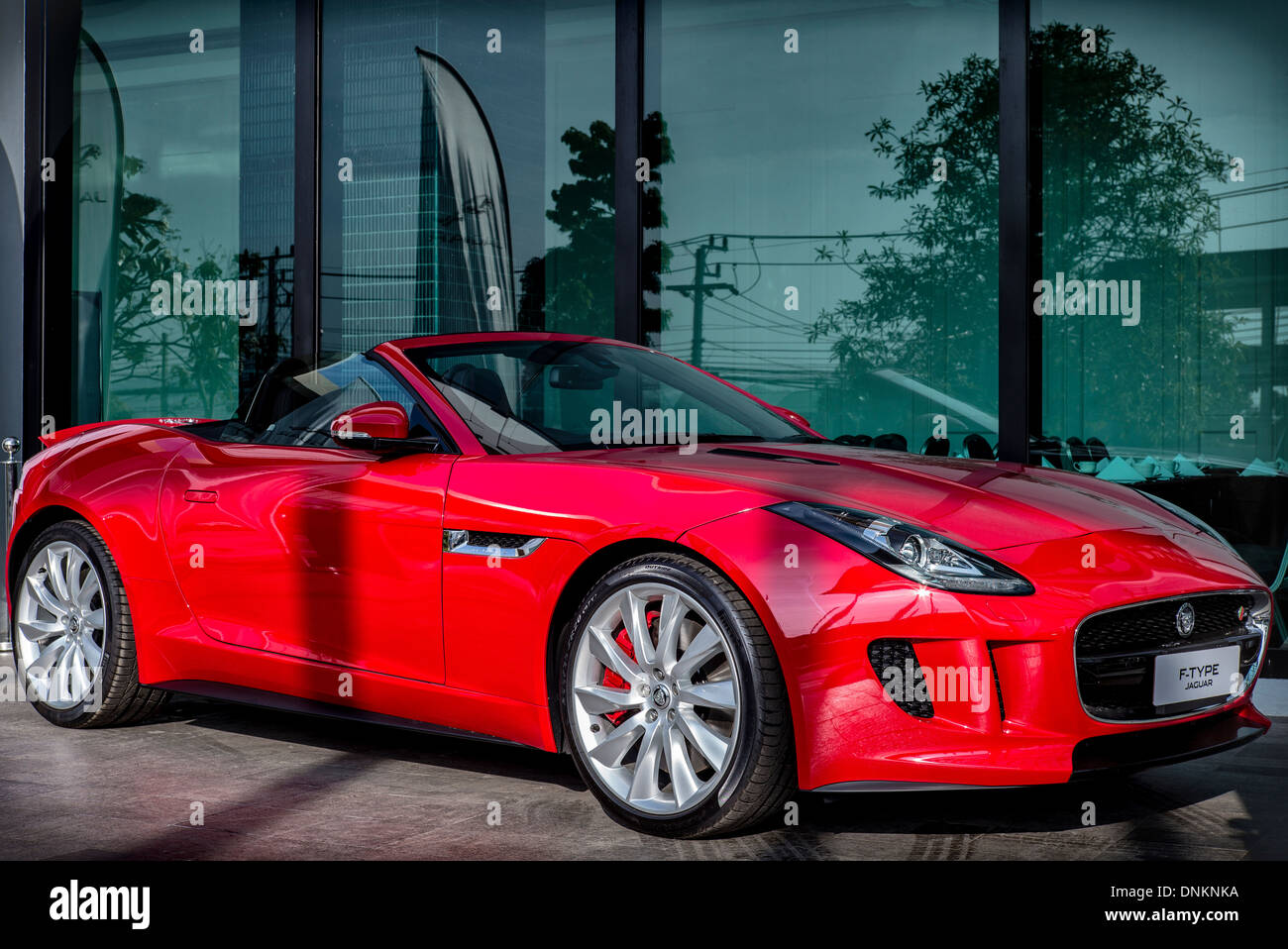 Full length side view of a red Jaguar F type British convertible sports car in red. - Stock Image
