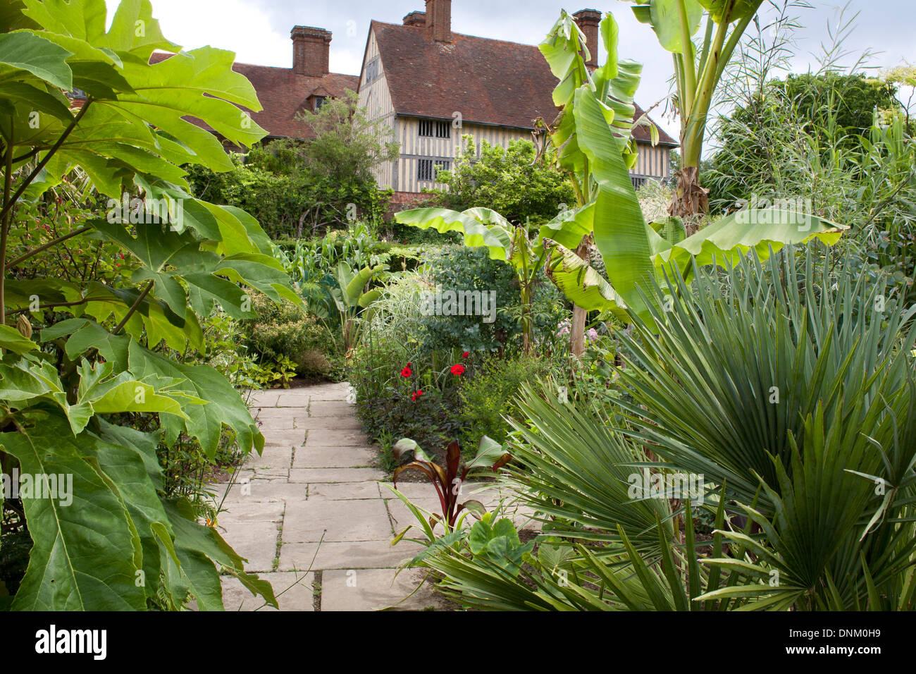 Path through exotic summer borders at Great Dixter, Sussex. Trachycarpus fortunei, Canna, Ricinus. Stock Photo