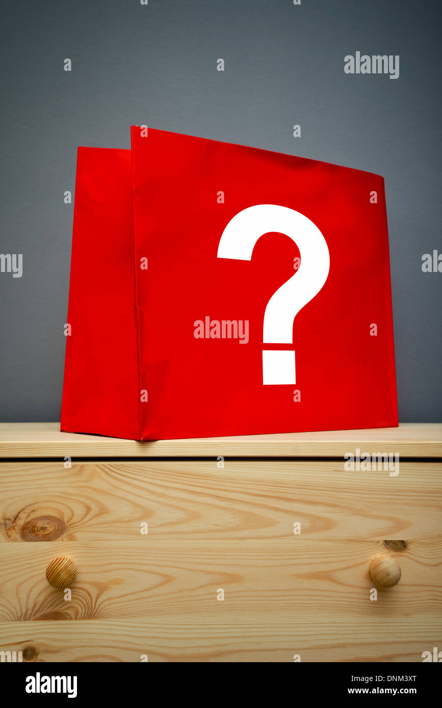 Red shopping bag with question mark on wooden cabinet - Stock Image