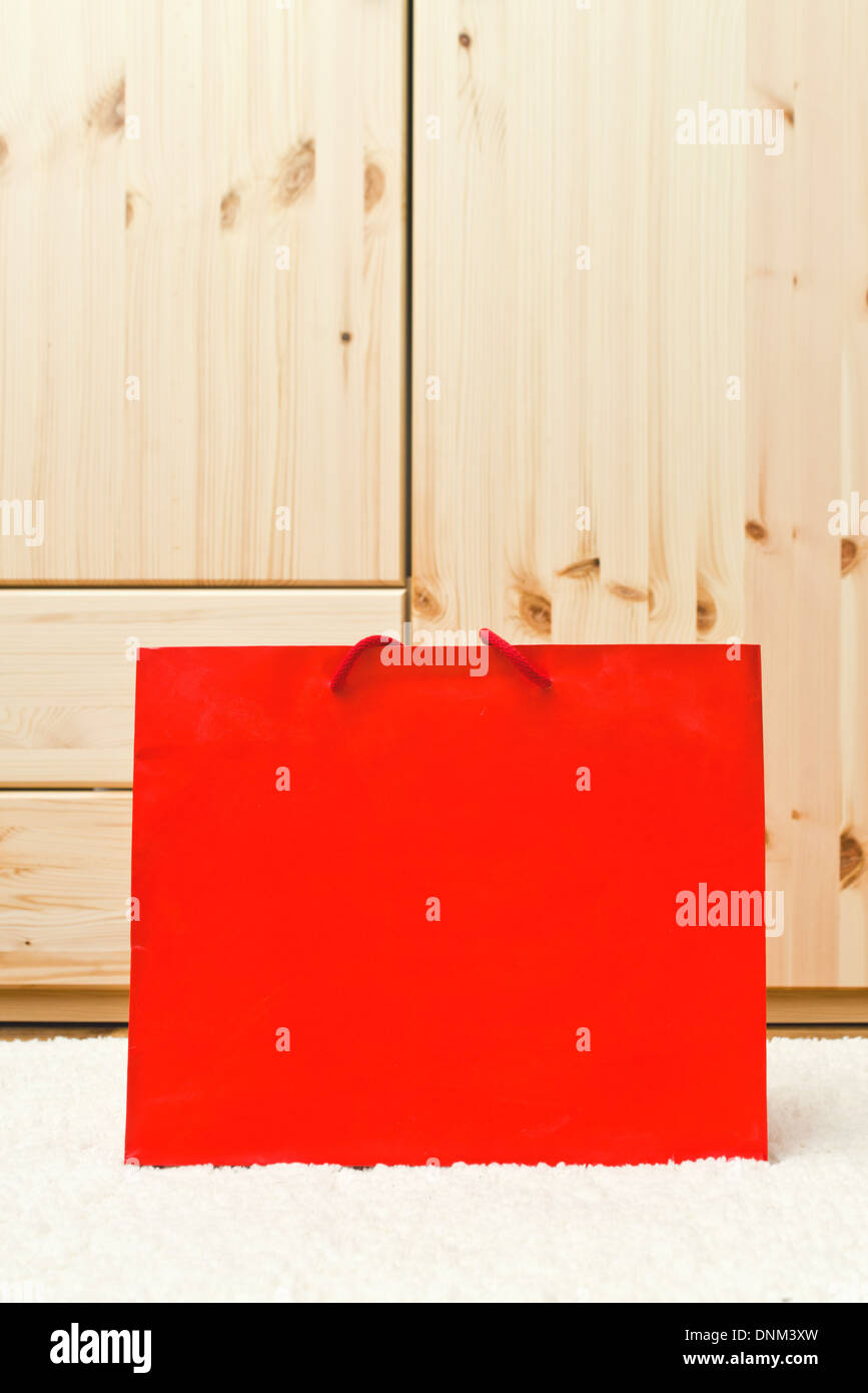 Red shopping bag in front of wooden cabinet. - Stock Image