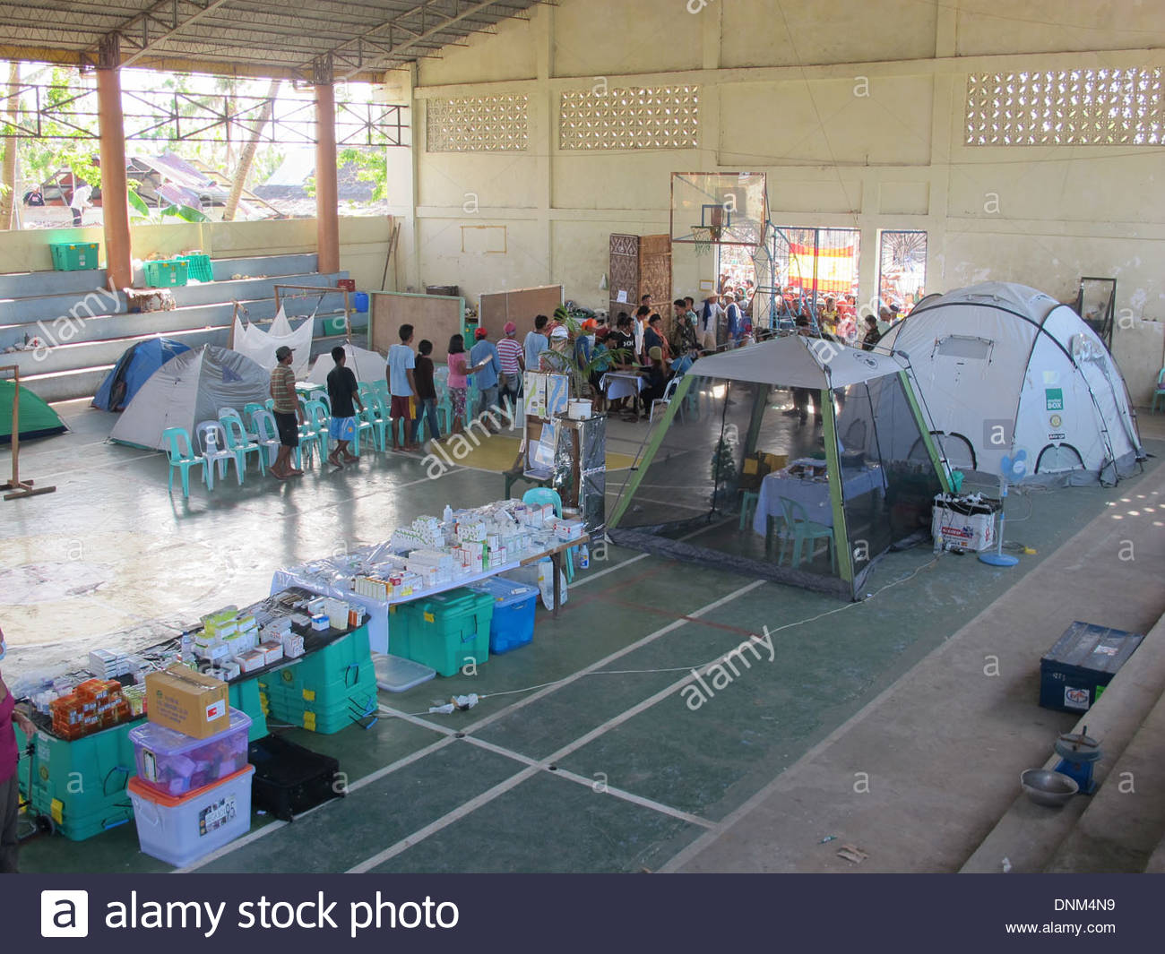 Food distribution line - queue in Bantayan.  People are waiting for bags of rice in an emergency medical facility. - Stock Image