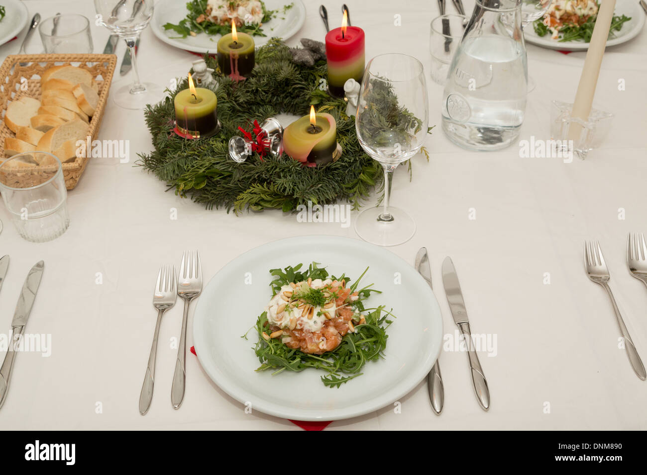 A photograph of a table setting at Christmas time. An entree of salmon tartar cream and roasted pine nuts has been served. & A photograph of a table setting at Christmas time. An entree of ...